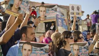 Protesters hold up photos of Khalid Saeed