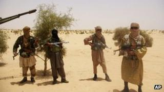 Fighters from Islamist group Ansar Dine stand guard during a hostage handover, in the desert outside Timbuktu, Mali, April 2012