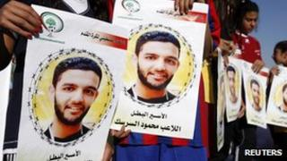 Palestinian girls holding pictures of detained footballer Mahmoud al-Sarsak