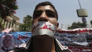 "A protester has his mouth taped with a bandage and words reading in Arabic ""Down with Shafik' during a protest outside the Supreme Constitutional Court, 14 June 2012"