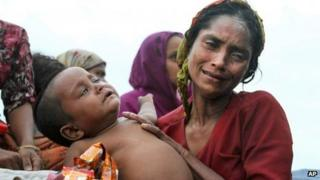 A Rohingya Muslim woman holds her baby on board that has been intercepted as it approached Bangladesh.