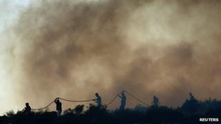 Firefighters and volunteers try to extinguish a forest fire at Thymari coastal village, 40 km (25 miles) southeast of Athens
