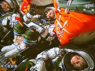 Chinese astronauts Jing Haipeng, Liu Wang and Liu Yang sit inside the Shenzhou-9 space capsule after launch, 16 June 2012