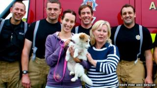 Tyex the dog and his owners with the fire crew who rescued him