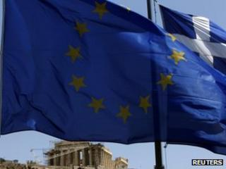 An EU and Greek flag flutter in front of the Parthenon, Athens