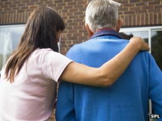 Woman helping an elderly man to his door