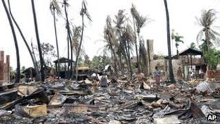 People shift through damaged buildings in Sittwe, capital of Rakhine state (16 June)