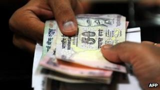Indian rupee notes being exchanged