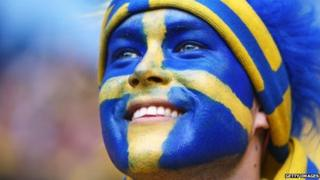 A man with the Swedish flag painted on his face
