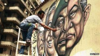 Man in Cairo paints mural depicting toppled President Hosni Mubarak (r) and current military ruler Mohammed Hussein Tantawi as two halves of one face (22 May)