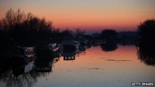 The sun sets over a canal in Slimbridge, England.
