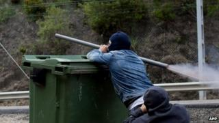 A Spanish miner on strike fires a homemade rocket-launcher over a wheelie bin in the northern Spanish town of Cinera