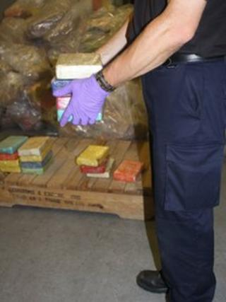 A UK border force officer holding some of the drugs
