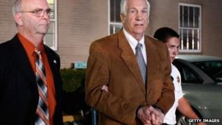 Former Penn State assistant football coach Jerry Sandusky (C) leaves the Centre County Courthouse in handcuffs after a jury found him guilty in his sex abuse trial on 22 June 2012 in Bellefonte, Pennsylvania, US