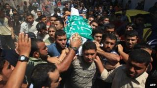 Men carry the body of a Palestinian militant killed in Gaza overnight (23 June 2012)