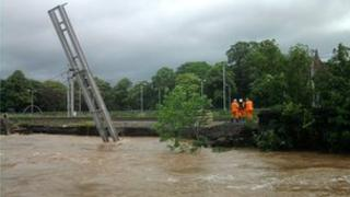 Overhead cable support for West Coast Mainline leans into the River Caldew