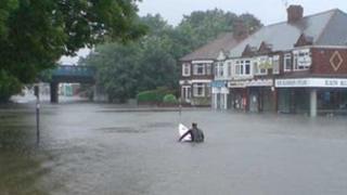 Man on surfboard in flooded Hull street