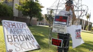 Jorge Mendez protests the Arizona immigration law outside the state capitol in Phoenix, Arizona 22 June 2012
