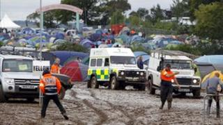 An ambulance is towed off the site at the Isle of Wight festival, after heavy rains turned the site into a mudbath causing traffic chaos.