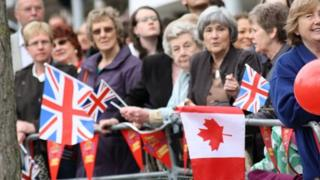 Crowds await the Queen's arrival