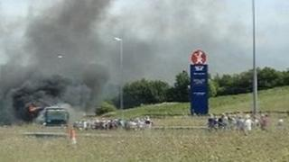 Smoke billows from the coach on fire on the A55