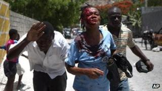 Bleeding woman is led to an ambulance after being hit by a stone during a demonstration in Port-au-Prince