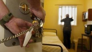 Prisoner in cell as warder locks the door
