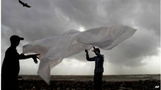 Indian washers try to fold a plastic sheet during a monsoon shower in Mumbai, India, Sunday, June 24, 2012.