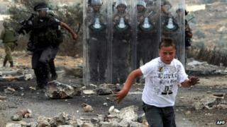 A Palestinian boy runs away from Israeli soldiers during protest against Israel near the West Bank city of Ramallah in 22 June 2012