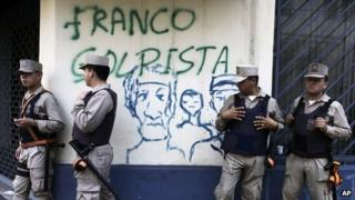 """Police officers stand in front of wall spray painted with a message that reads in Spanish: """"Franco, coupmonger,"""" referring to newly named president Federico Franco"""