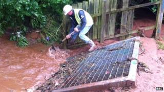 Worker clears mud from drain