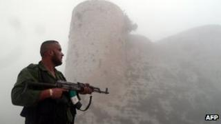 """A member of the Free Syrian Army stands near the """"Al-Hosn"""" Crusaders Citadel on the outskirts of flashpoint city of Homs"""