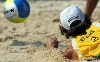 Brazilian player dives for the ball in beach volleyball tournament at Beijing Olympics, 2008