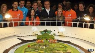 """Danny Boyle (centre) with Olympic volunteers and a model of the """"British countryside"""" set"""