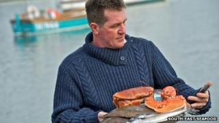 A fisherman holding seafood and a smart phone