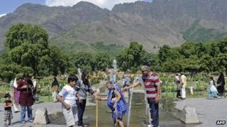 Tourists cool down at a fountain in Kashmir