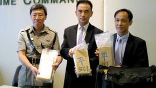Hong Kong customs officials show the cocaine seized on 4 July to the media, 6 July 2012