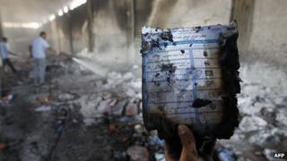 A man holds up a burnt ballot paper as Libyan firemen extinguish a fire at a warehouse that was used by the election committee for storing materials for the upcoming General National Congress elections in the eastern city of Ajdabiya on 5 July 2012