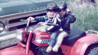 Steven and Chris on a quad bike, wearing helmets