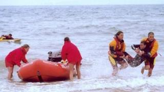 Two lifeguards carrying a 'casualty' from the water