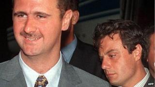 Manaf Tlass, (R), behind Syrian president Bashar al-Assad in 1999