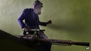 A Sri Lankan municipal worker walks down stairs after fumigating for a public housing scheme in an attempt to control dengue fever in Colombo (File)