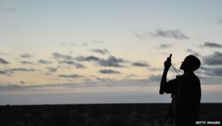 An African man holds up his mobile to get signal