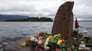 Flowers and candles are placed on the shore opposite to the Utoeya Island, Norway, Sunday, July 24, 2011