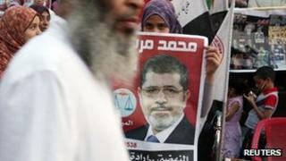 A supporter holds a poster of Egypt's President Mohammed Mursi at Tahrir Square in Cairo 10 July