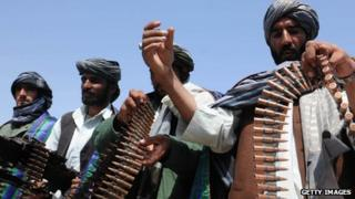 Former Taliban fighters display their weapons as they join Afghan government forces during a ceremony in Herat province on 26 April 2012