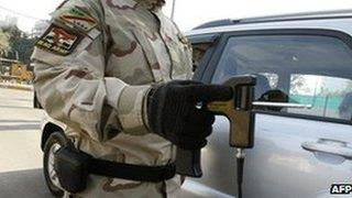 An Iraqi soldier using a 'bomb detecting' device at a checkpoint in Baghdad on January 23 2010
