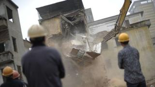 Chinese construction workers oversee a house being demolished