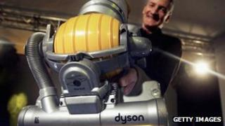 James Dyson holds up a new model of vacuum cleaner