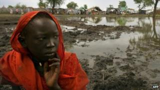 A Sudanese refugee sits by a flooded area of Jamam refugee camp, South Sudan, 15 July 2012